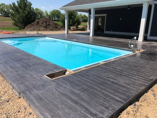 Poured and stamped concrete surrounding in-ground pool