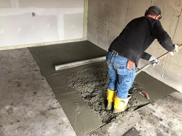 Man smoothing concrete floor